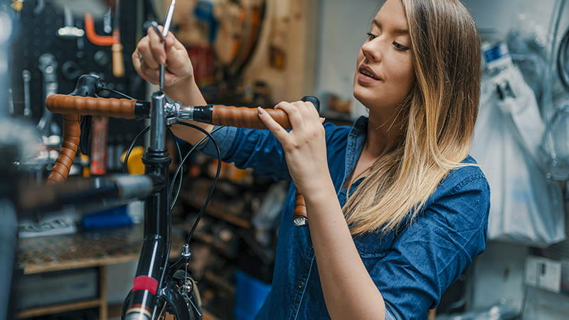 Woman repairing bike in bike shop